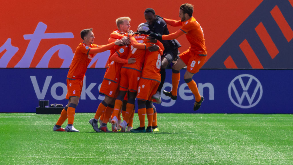 Kadell Thomas celebrates with teammates after scoring the first goal in Forge FC history. (David Grif/CPL)