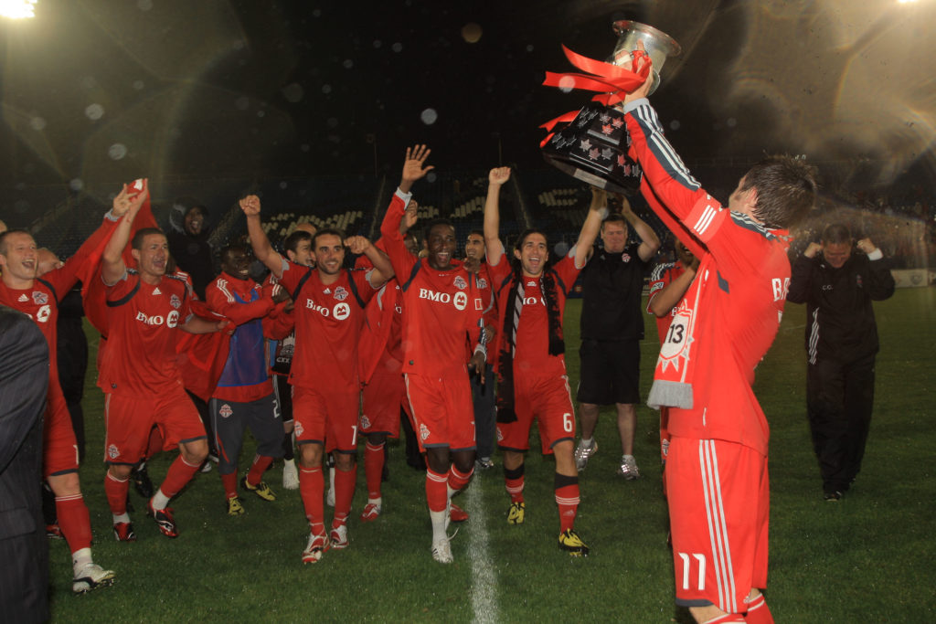 Former Toronto FC captain and current York9 FC head coach Jimmy Brennan lifts the Voyageurs Cup. (Photo: Canada Soccer).