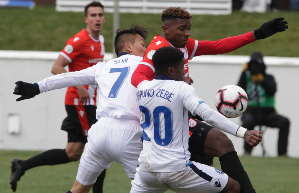 Dominique Malonga of Cavalry FC fights off Son Yongchan and Bruno Zebie of FC Edmonton. Photo: Jack Cusano/CPL).