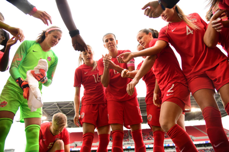 Christine Sinclair (12, C) leads the huddle during a friendly in Toronto. (Photo: Martin Bazyl/Canada Soccer).