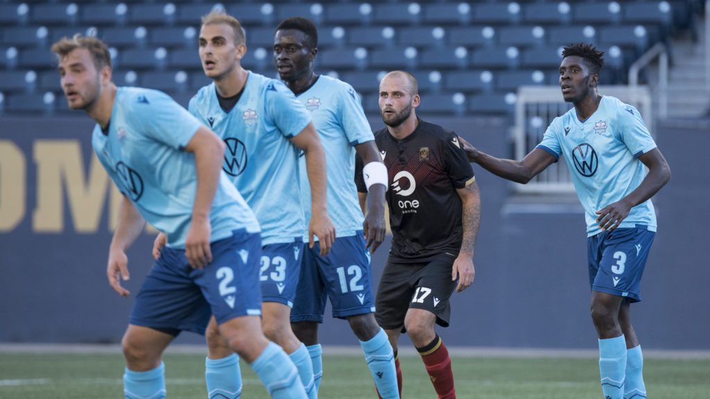 HFX Wanderers players and Valour FC striker Stephen Hoyle wait for a set piece. (CPL).