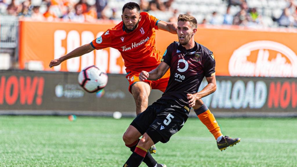 Forge FC's David Choinière fires a shot past Valour FC midfielder Louis Béland-Goyette. (Ryan McCullough/CPL).