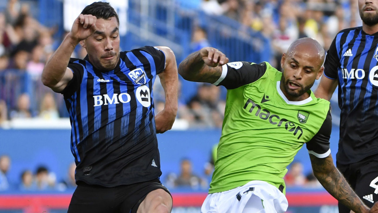 Jul 24, 2019; Montreal, Quebec, Canada; York9 FC defender Kyle Porter (19) battles the ball with Montreal Impact defender Daniel Lovitz (3) and Montreal Impact Rudy Camacho (4) during the first half at Saputo Stadium. Mandatory Credit: Eric Bolte-USA TODAY Sports