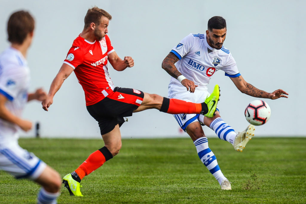 Cavalry FC attacker Nico Pasquotti (17) and Montreal Impact defender Jorge Corrales (26) battle for the ball during the first half during the Canadian Championship Semi-final soccer match at Spruce Meadows. Mandatory Credit: Sergei Belski-USA TODAY Sports for CPL