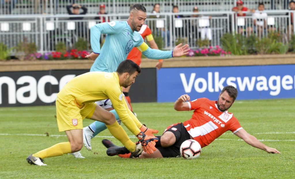 Marco Carducci of Cavalry FC and Jonathan Wheeldon of Cavalry FC scramble to keep the ball away from Marcus Haber of Pacific FC. Mike Sturk/CPL