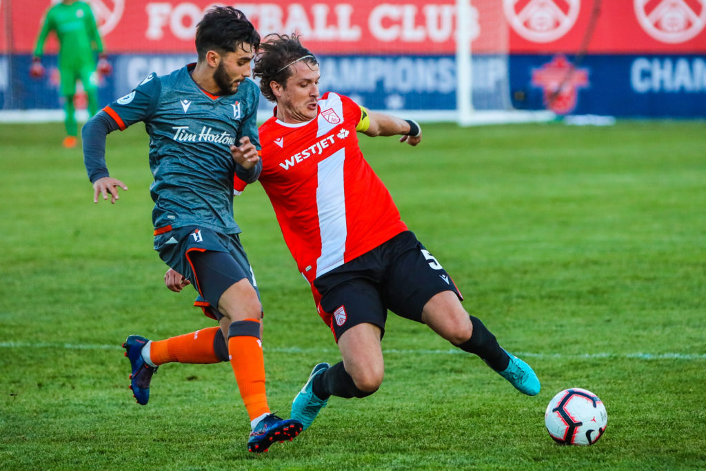 Cavalry FC defender Mason Trafford (5) and Forge FC midfielder Tristan Borges (19) battle for the ball in the second half during a match at ATCO Field, Spruce Meadows. (Photo: Sergei Belski-USA TODAY Sports).