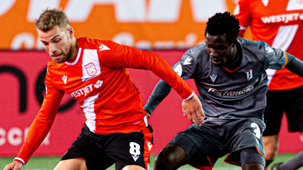 Cavalry FC midfielder Julian Buescher battles for the ball with Forge FC midfielder Elimane Cisse. Photo: Ryan McCullough/CPL