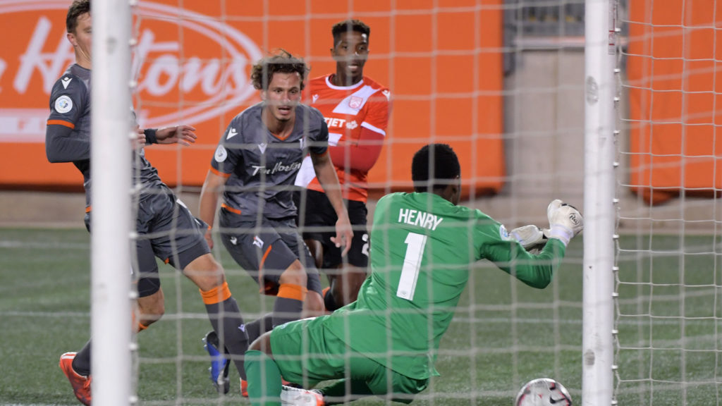 Forge FC goalkeeper Triston Henry makes a save on a shot from Cavalry FC's Dominique Malonga. (Mandatory Credit: Dan Hamilton-USA TODAY Sports for CPL).