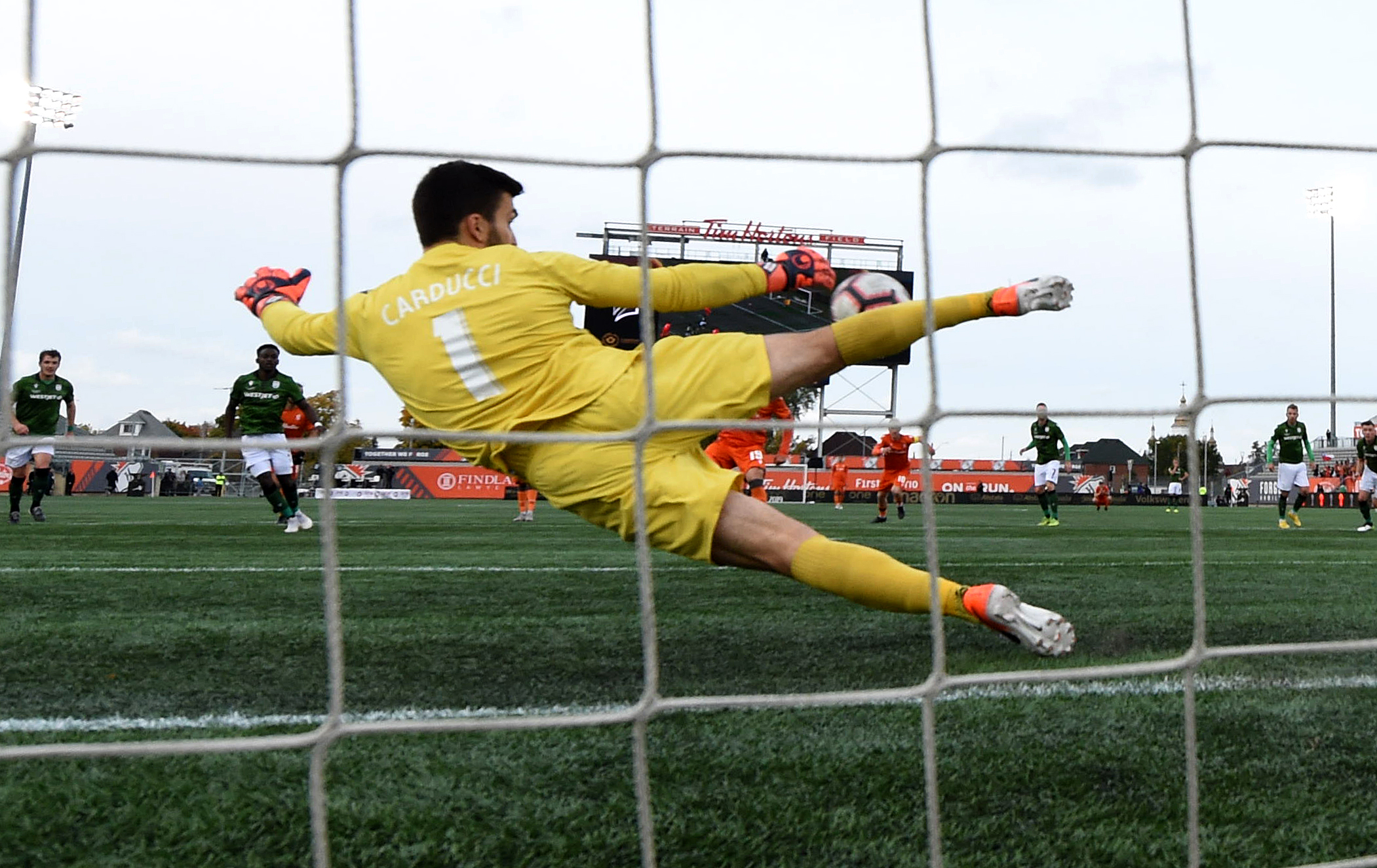 Oct 26, 2019; Hamilton, Ontario, CAN; Cavalry FC goalkeeper Marco Carducci (1) makes a save on a penalty kick against Forge FC in the first half of a Canadian Premier League soccer final match at Tim Hortons Field. Mandatory Credit: Dan Hamilton-USA TODAY Sports for CPL