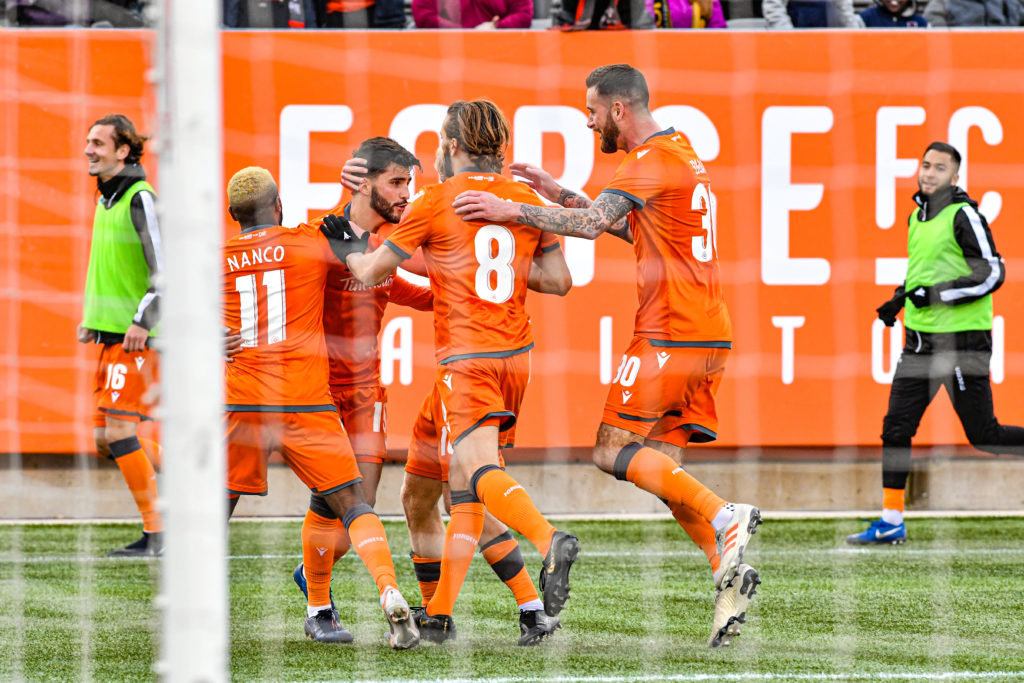 Forge FC players converge on Tristan Borges after his first-half goal put them 1-0 up on Cavalry FC. (Photo: CPL)