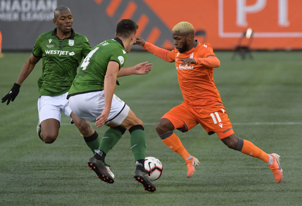 Oct 26, 2019; Hamilton, Ontario, CAN; Forge FC forward Christopher Nanco (11) dribbles the ball between Cavalry FC defender Dominick Zator (4) and forward Jordan Brown (9, left) in the second half of a Canadian Premier League soccer final match at Tim Hortons Field. Mandatory Credit: Dan Hamilton-USA TODAY Sports for CPL