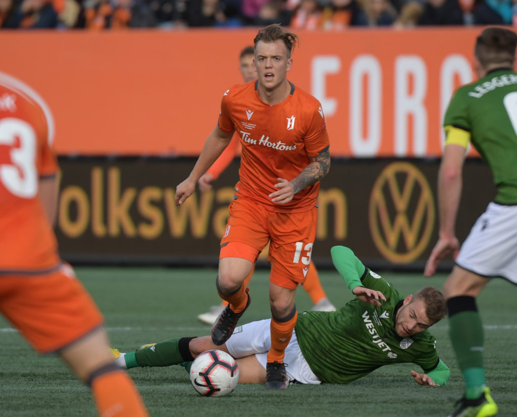 Oct 26, 2019; Hamilton, Ontario, CAN; Forge FC midfielder Alexander Achinioti-Jonsson (13) dribbles the ball away from Cavalry FC midfielder Julian Buscher (8) in the first half of a Canadian Premier League soccer final match at Tim Hortons Field. Mandatory Credit: Dan Hamilton-USA TODAY Sports for CPL