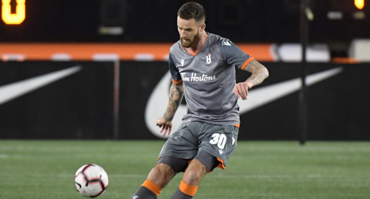 Oct 16, 2019; Hamilton, Ontario, CAN; Forge FC defender David Edgar (30) hits a pass against Cavalry FC in the first half of a Canadian Premier League soccer match at Tim Hortons Field. Mandatory Credit: Dan Hamilton-USA TODAY Sports for CPL