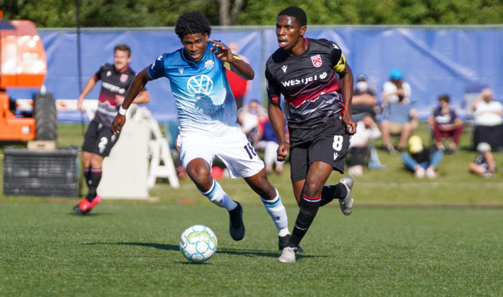 Andre Rampersad of HFX Wanderers dribbles past Elijah Adekugbe of Cavalry. (CPL/Chant Photography)