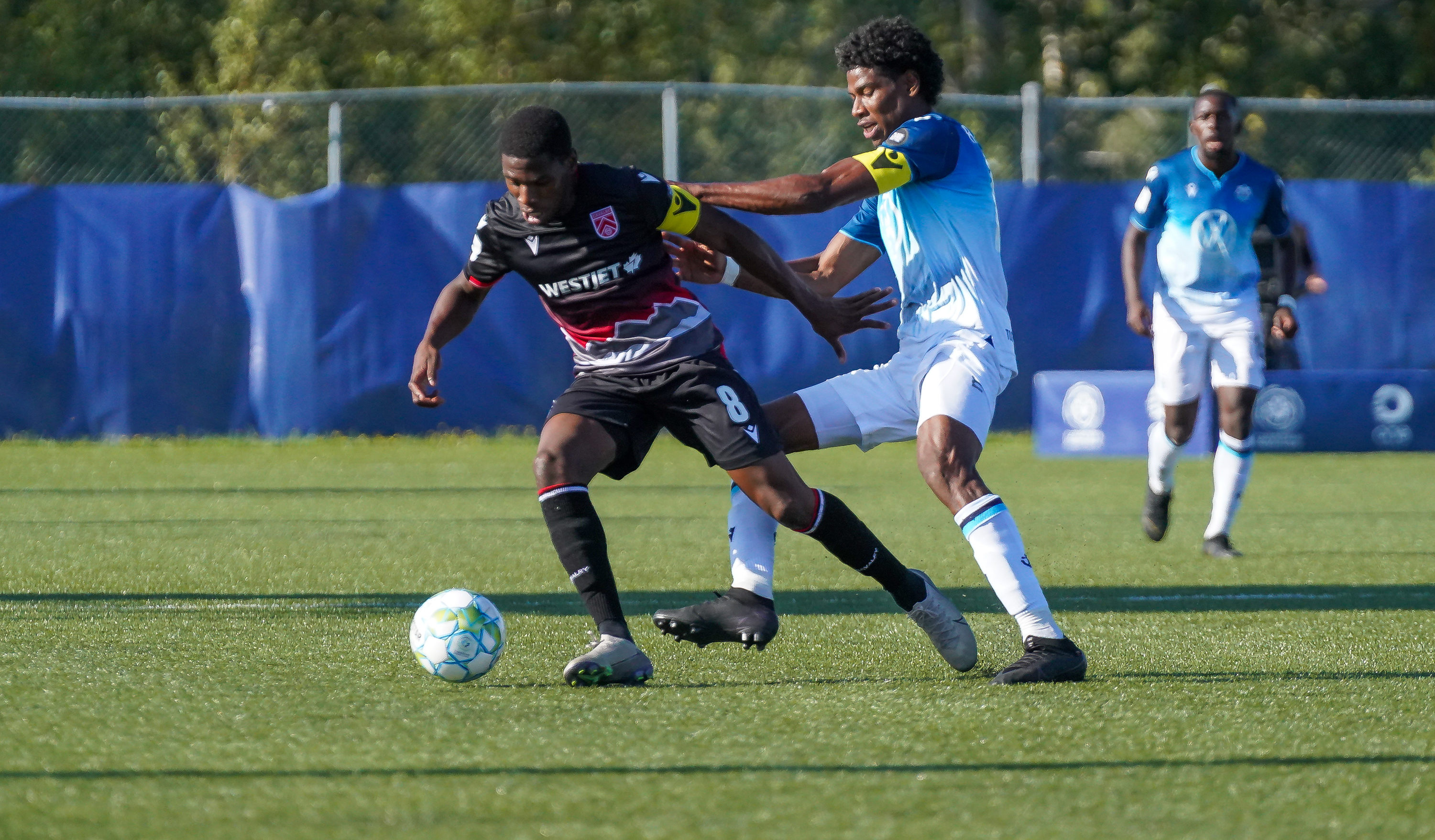 Cavalry FC's Elijah Adekugbe battles with Andre Rampersad of HFX Wanderers FC. (CPL/Chant Photography)
