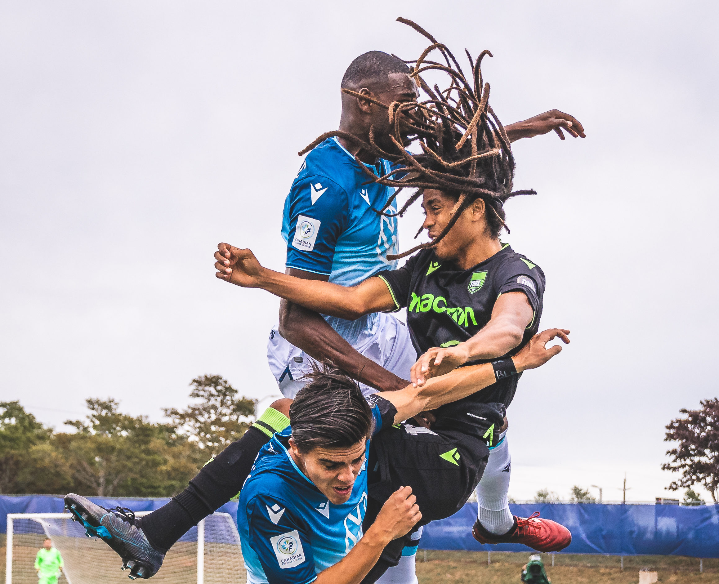 York9's Ijah Halley (and his hair) collides with HFX Wanderers defenders mid-air. (CPL/Chant Photography)