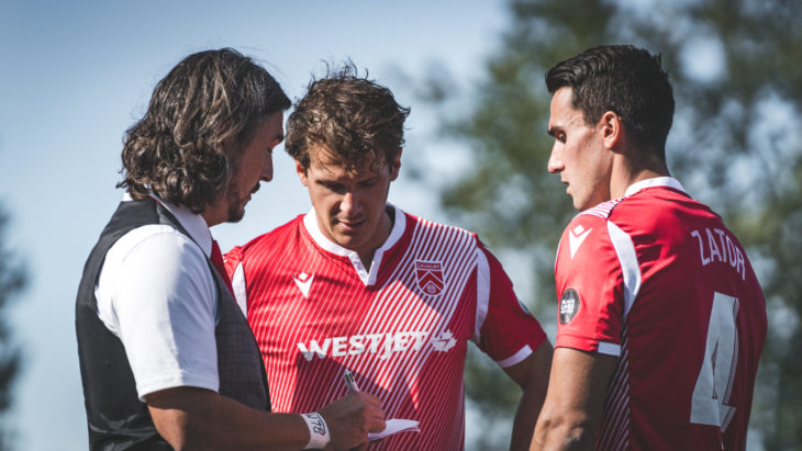 Cavalry FC coach Tommy Wheeldon Jr. gives instructions to Mason Trafford (centre) and Dominick Zator (right). (Photo: CPL/Chant Photography)
