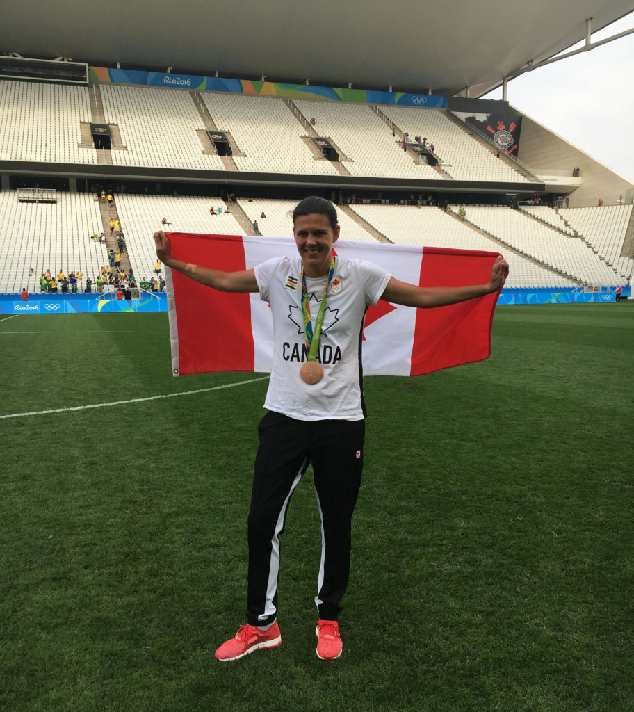 Christine Sinclair with a Canada flag after winning the bronze-medal game at Rio 2016 (Photo: Canada Soccer)