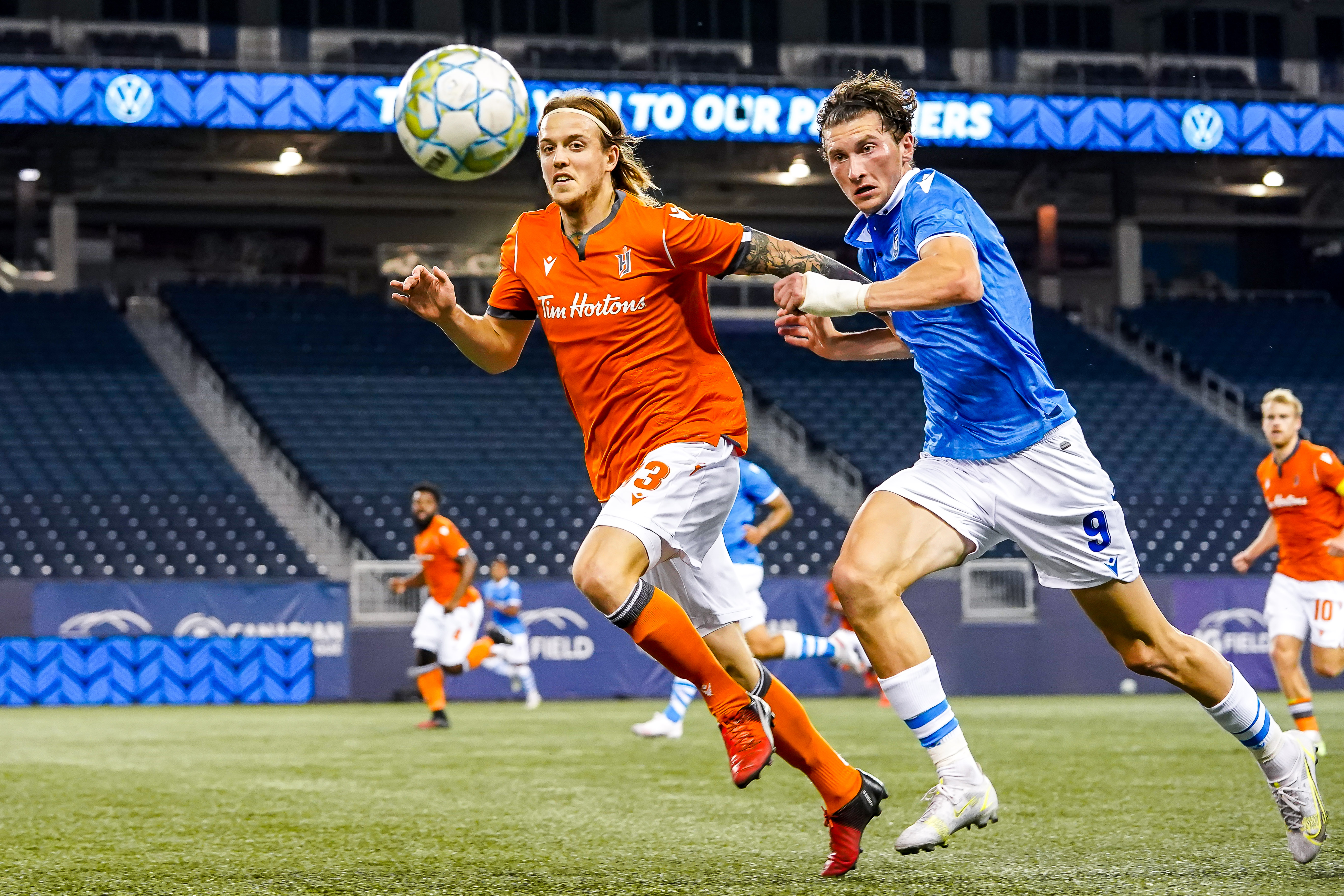 July 14, 2021. Forge FC vs FC Edmonton. First-Half. Alexander Achinioti-Jönsson of Forge FC and Easton Ongaro of FC Edmonton chase the loose ball.