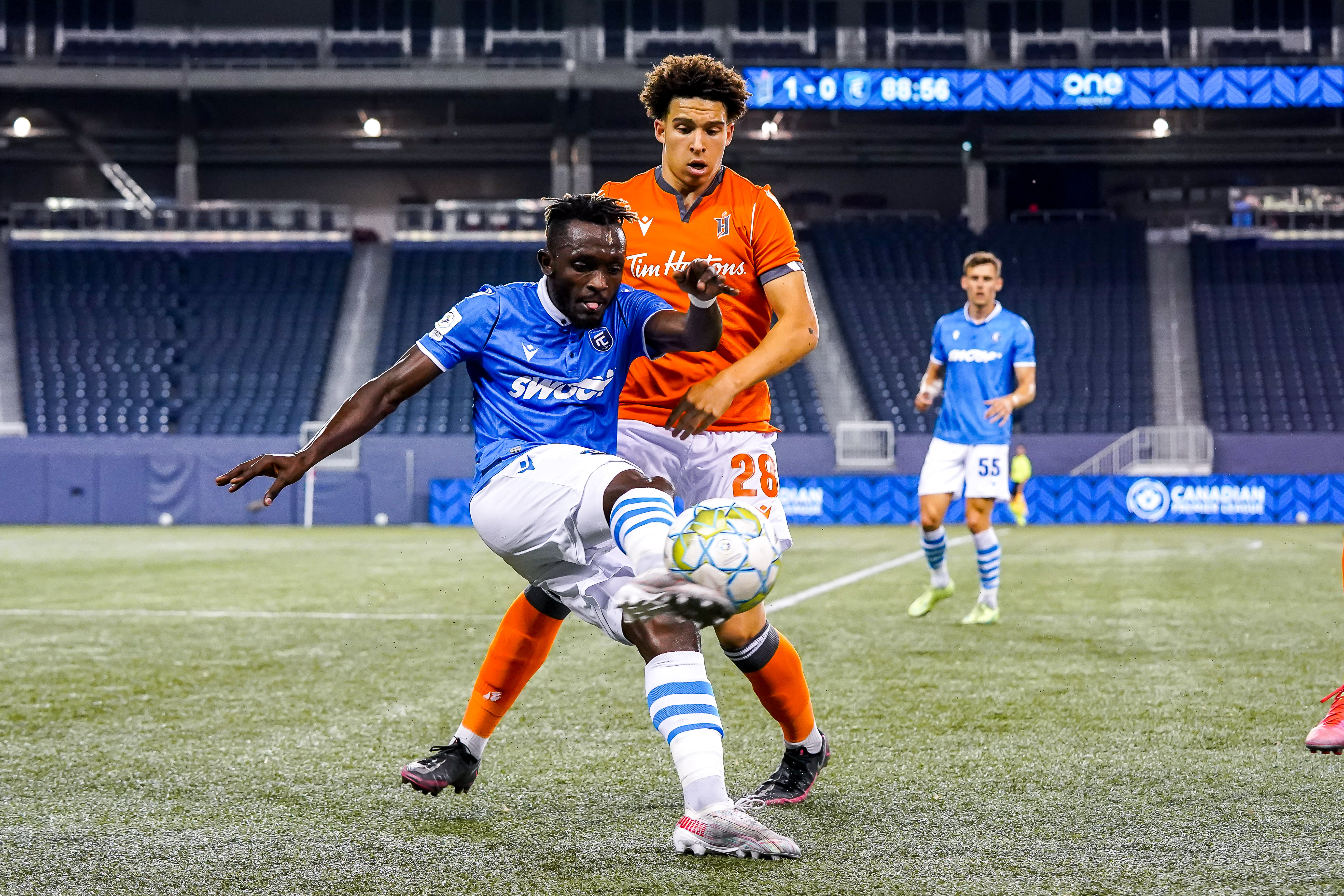 July 14, 2021. Forge FC vs FC Edmonton. Second-Half. Jeannot Esua of FC Edmonton plays the ball away from Robert Cleary of Forge FC.