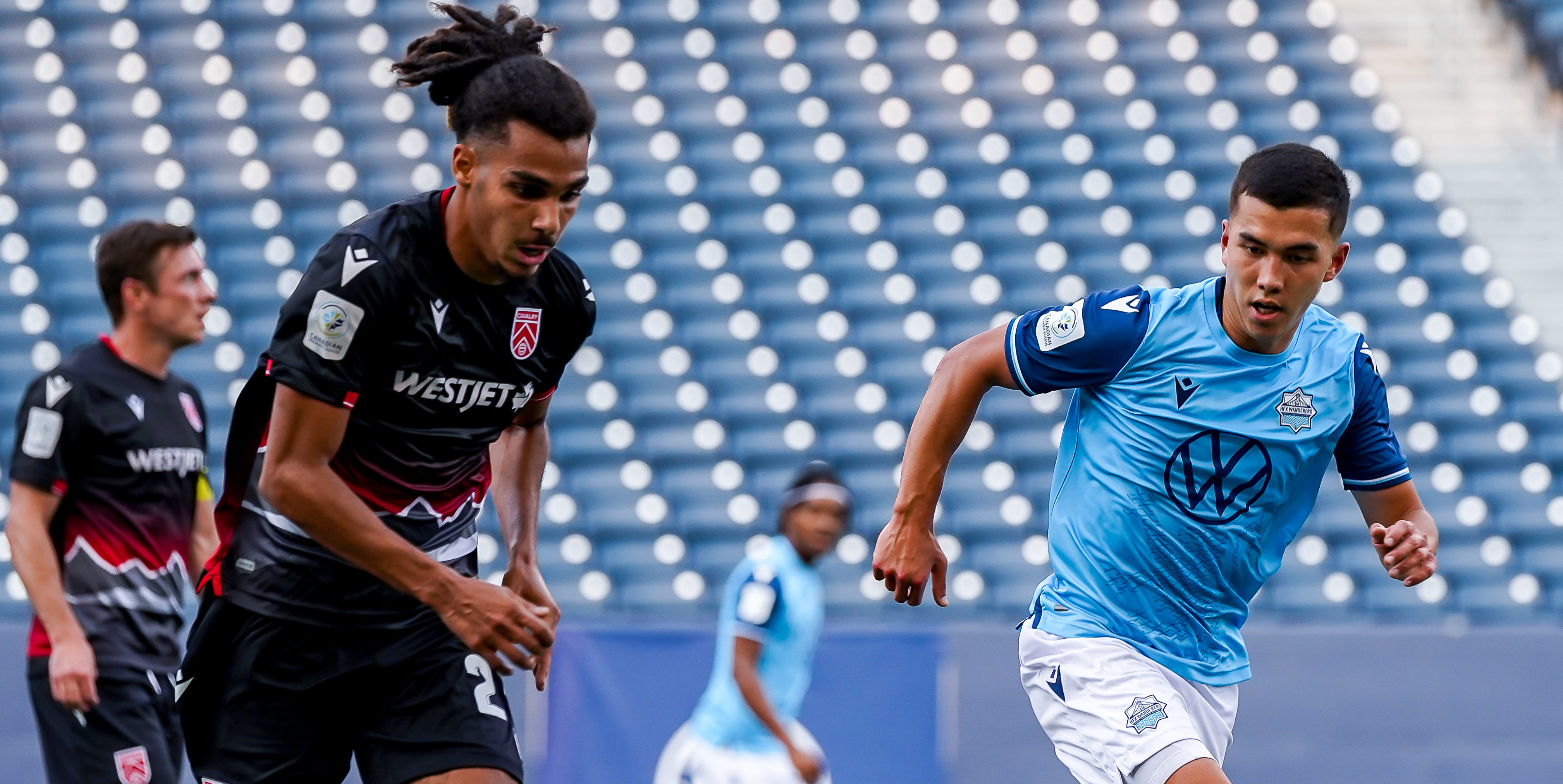 July 17, 2021. HFX Wanderers FC vs Cavalry FC. First-Half. Mohamed Farsi of Cavalry FC and Pierre Lamothe of HFX Wanderers FC chase the loose ball. (CPL)