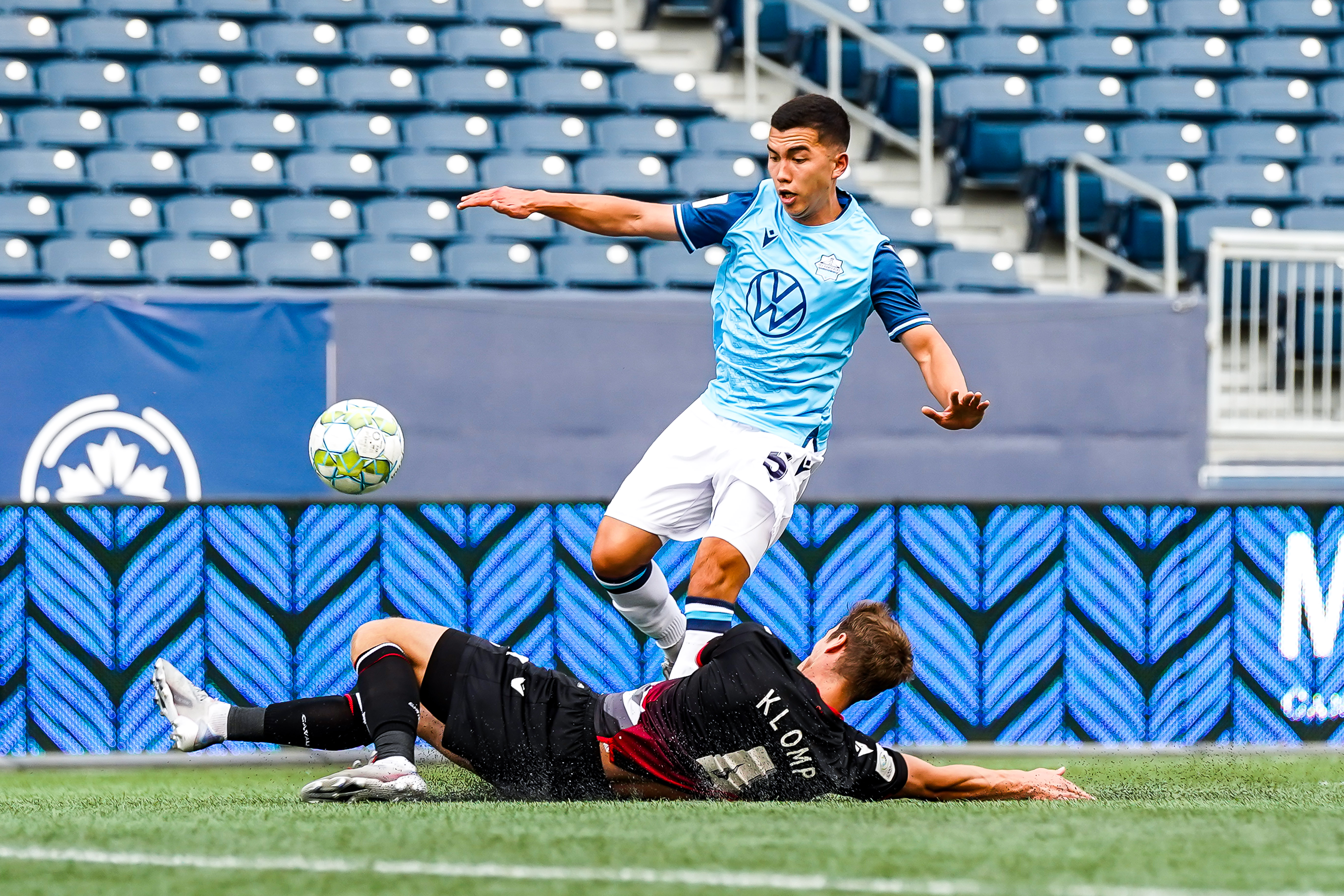 July 17, 2021. HFX Wanderers FC vs Cavalry FC. First-Half. Daan Klomp of Cavalry FC makes a sliding tackle in front of Pierre Lamothe of HFX Wanderers FC.