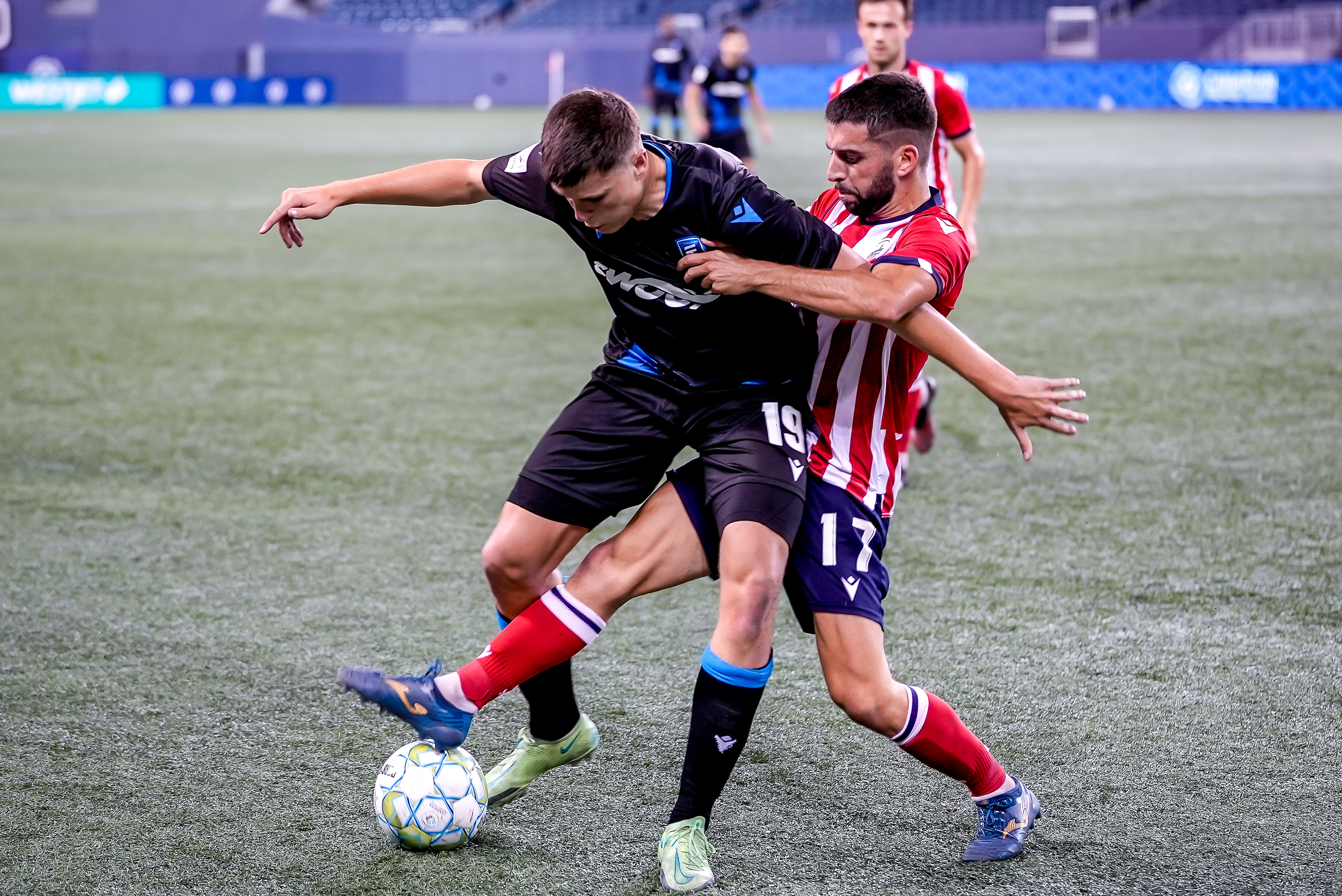 July 18, 2021. Atlético Ottawa vs FC Edmonton. Second-Half. Tobias Warschewski of FC Edmonton keeps the ball away from Miguel Acosta of Atlético Ottawa.