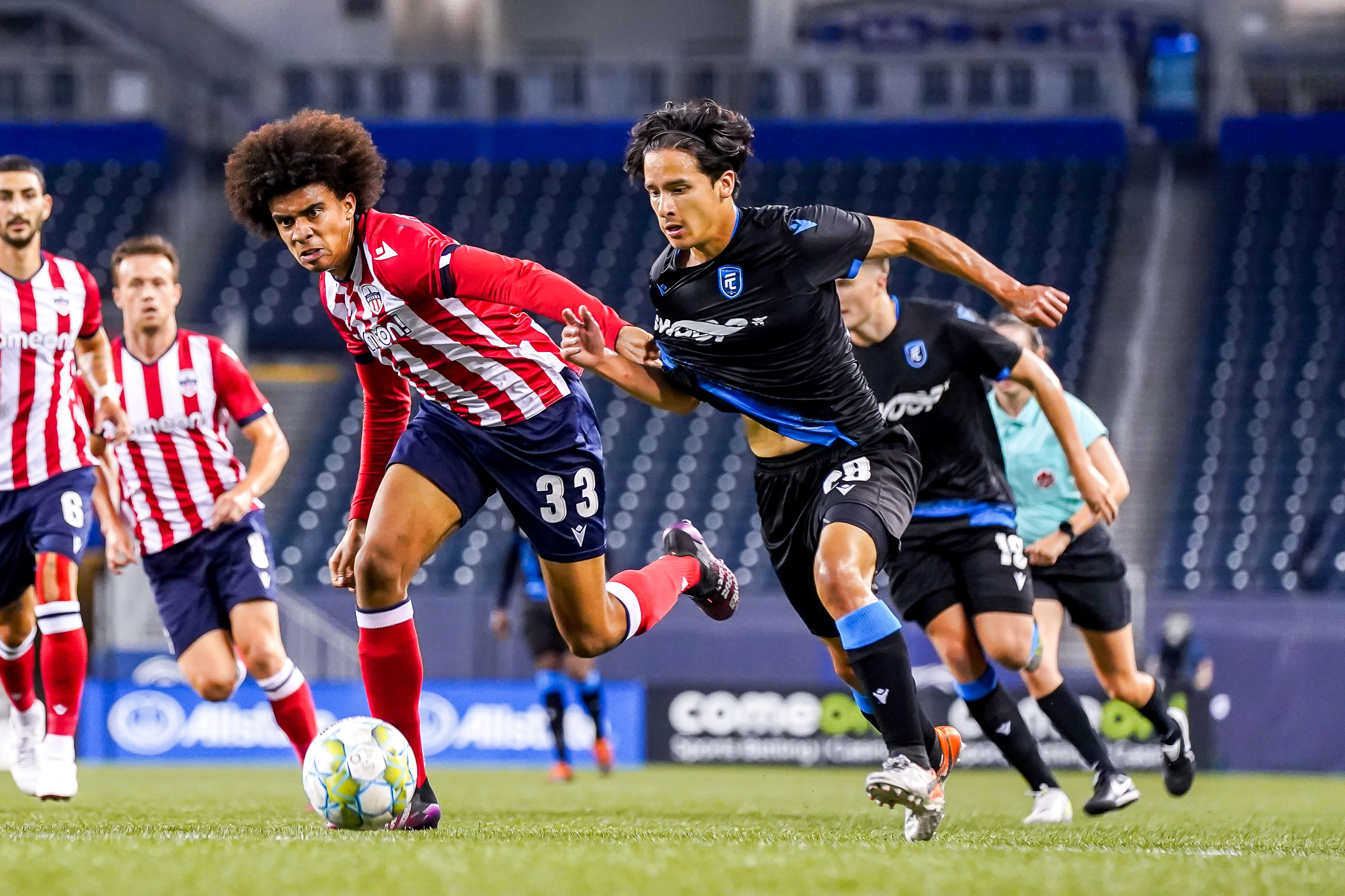 July 18, 2021. Atlético Ottawa vs FC Edmonton. First-Half. Keesean Ferdinand of Atlético Ottawa and Thomas Gardner of FC Edmonton chase the loose ball.