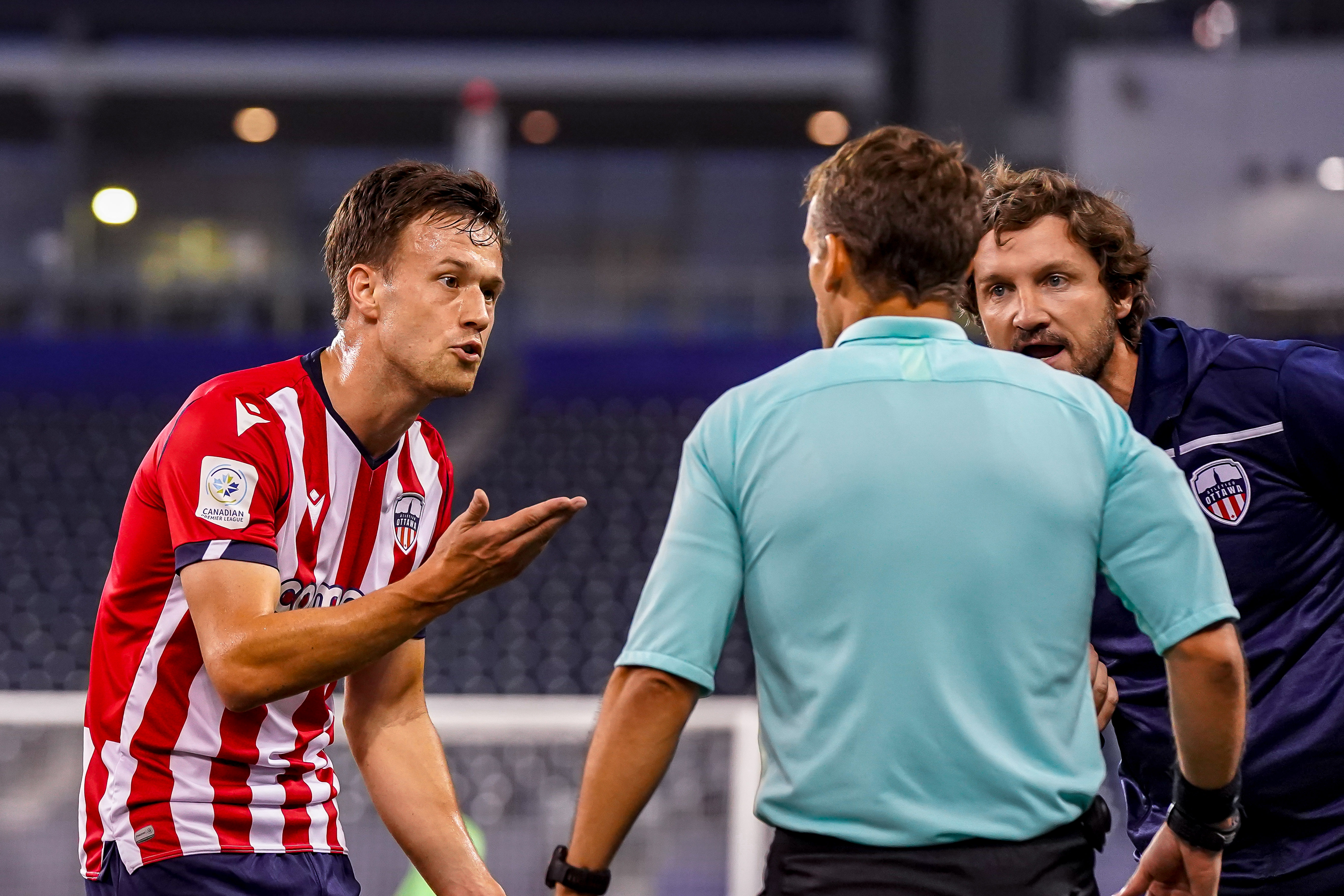 July 21, 2021. Pacific FC vs Atlético Ottawa. First-Half. Ben McKendry and Head Coach Mista of Atlético Ottawa argue a red card issued to McKendry in the first-half.