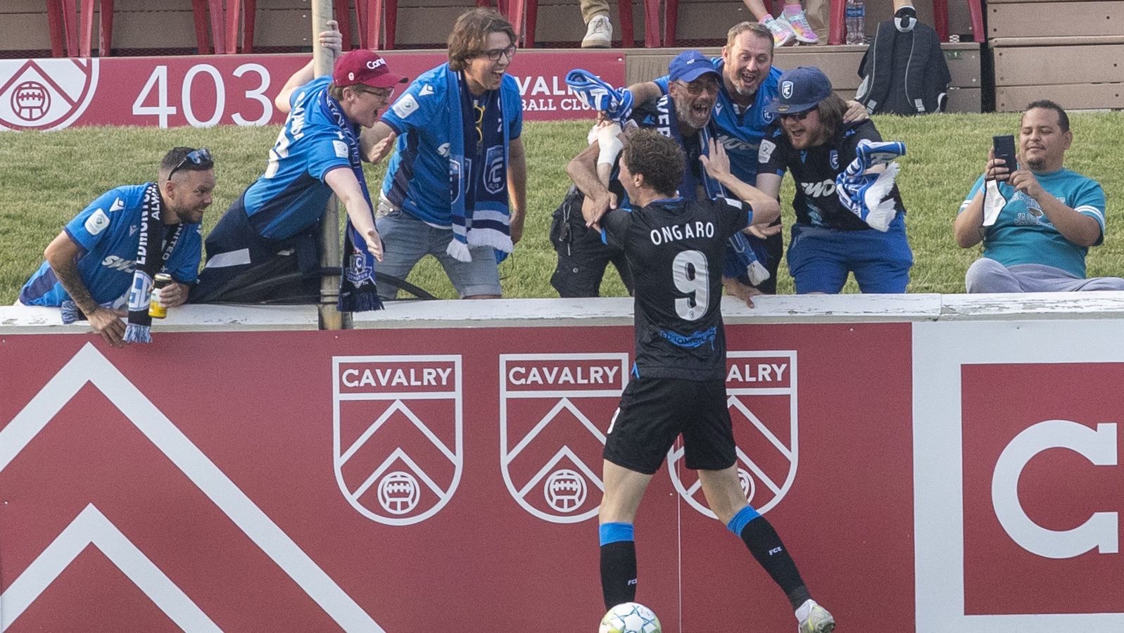 FC Edmonton attacker Easton Ongaro celebrates with FC Edmonton's travelling supporters after scoring the games' first goal in the match betweenin the match Cavalry FC vs FC Edmonton at ATCO Field, Calgary, Alberta, Canada - Aug 3, 2021 (Tony Lewis/CPL)
