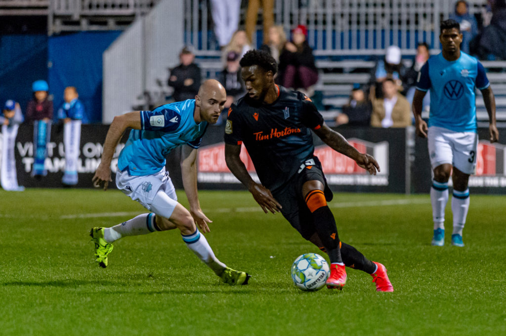 Forge FC attacker Omar Browne tries to escape from HFX Wanderers FC midfielder Jeremy Gagnon-Lapare during the match between HFX Wanderers FC and Forge FC at the Wanderers Grounds in Halifax, Nova Scotia. (Trevor MacMillan/HFX Wanderers FC)