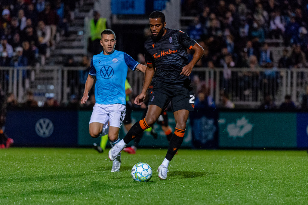 Halifax, Nova Scotia - Oct 06, 2021: Forge FC Defender, Jonathan Grant (2) looks to pass the ball as HFX Wanderers FC Midfielder, Pierre Lamothe (5) challenges during the match between HFX Wanderers FC and Forge FC at the Wanderers Grounds in Halifax, Nova Scotia. (Trevor MacMillan/HFX Wanderers FC)