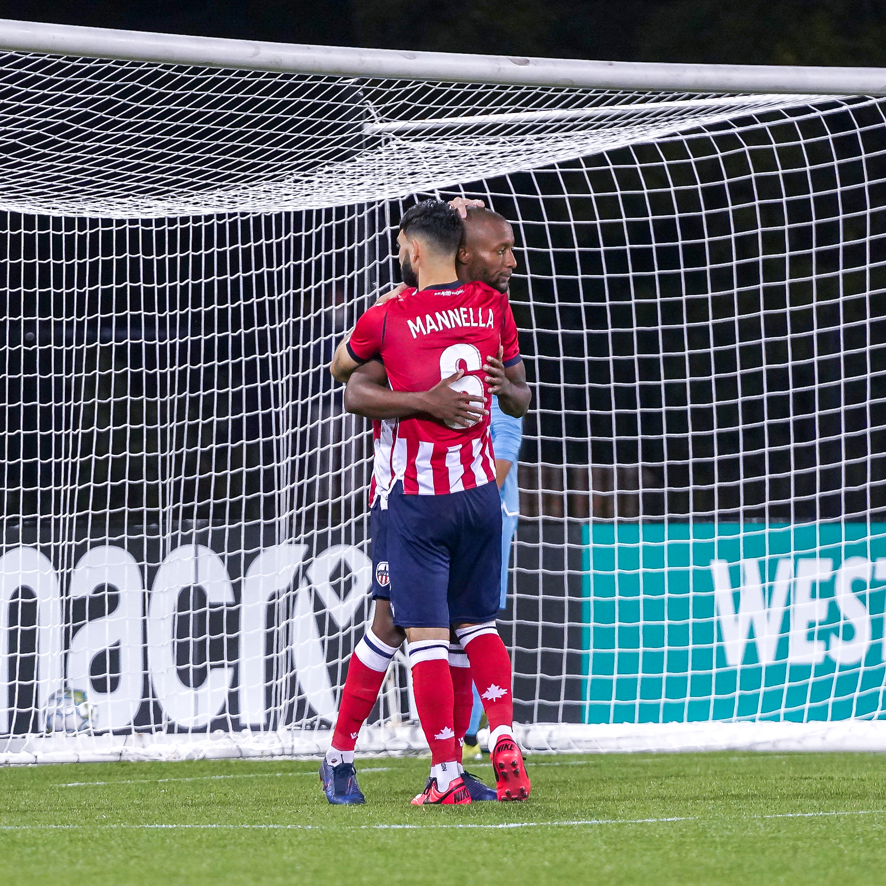 Malcolm Shaw and Chris Mannella embrace after the former scores a penalty vs. York United. (York United/CPL)
